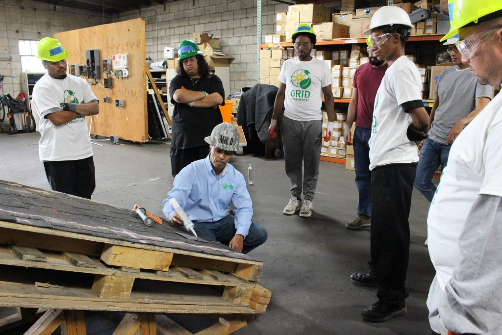 Participants in a training held by GRID Alternatives in the Los Angles area learn about solar installation on a mock roof. Photo courtesy of GRID Alternatives