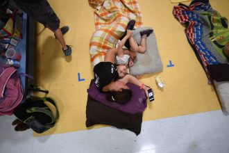 Evacuees rest in a makeshift shelter at an elementary school in Florida ahead of Hurricane Matthew in 2016. Credit: Jewel Samad/AFP via Getty Images