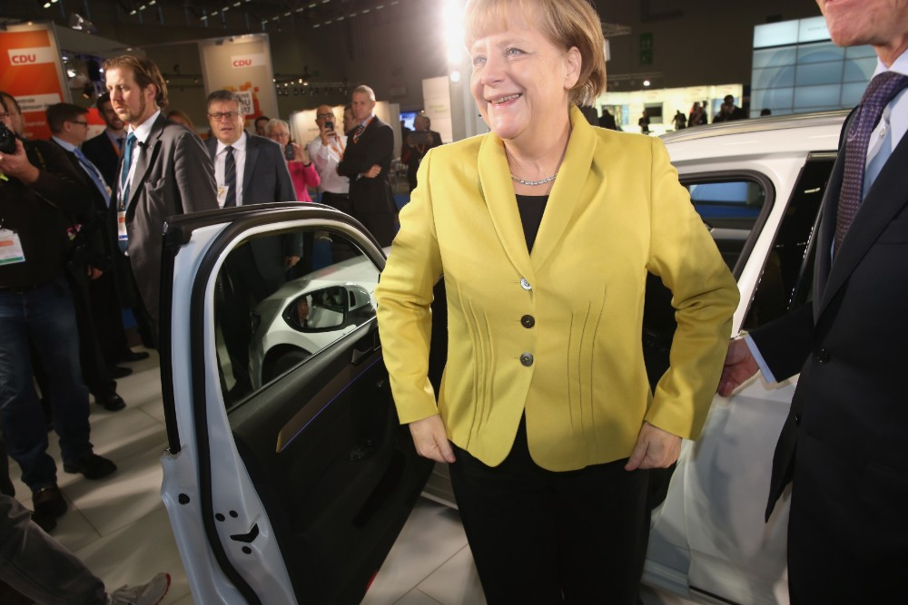 German Chancellor Angela Merkel steps out of Volkswagen Passat GTE plug-in hybrid car at a 2014 event for her party, the Christian Democrats. Merkel has been a staunch defender of her country's auto industry.  Credit: Sean Gallup/Getty Images