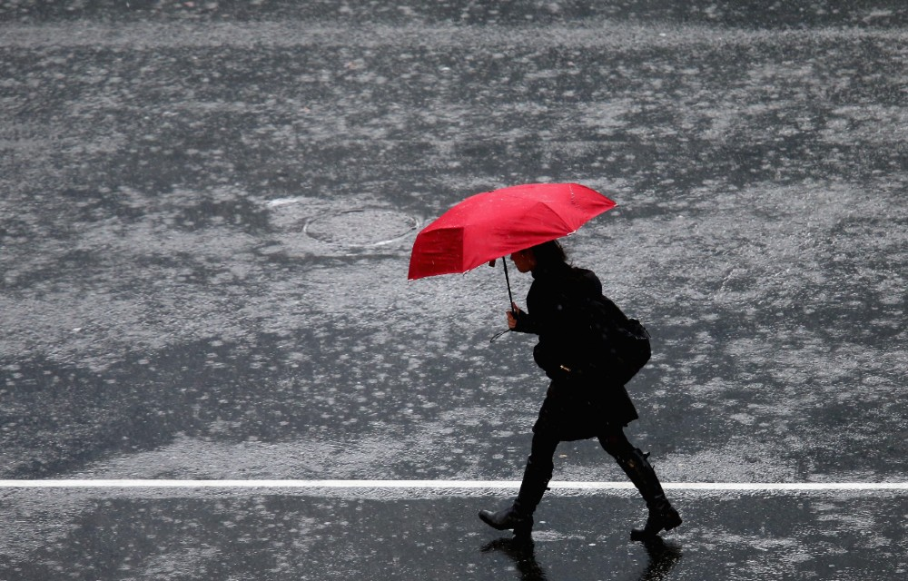 A pedestrian crosses in the intersection of Queen Street and Victoria Street during heavy rain in Auckland, New Zealand. Credit: Jason Oxenham/Getty Images