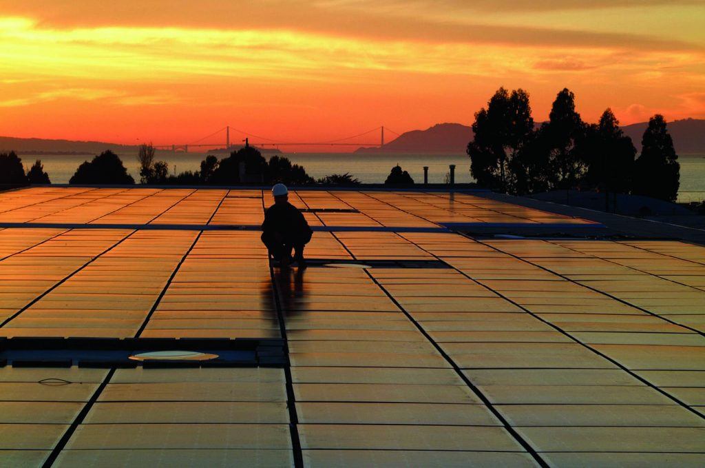 Workers lay rooftop solar panels in San Francisco. Credit: SunPower/NREL