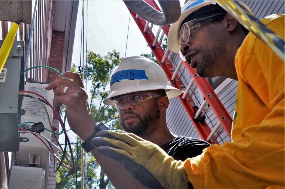 A trainer works with a student at a 2019 solar install in Washington, D.C. overseen by GRID Alternatives, a national nonprofit that makes renewable energy and job training accessible to underserved communities. Courtesy of GRID Alternatives