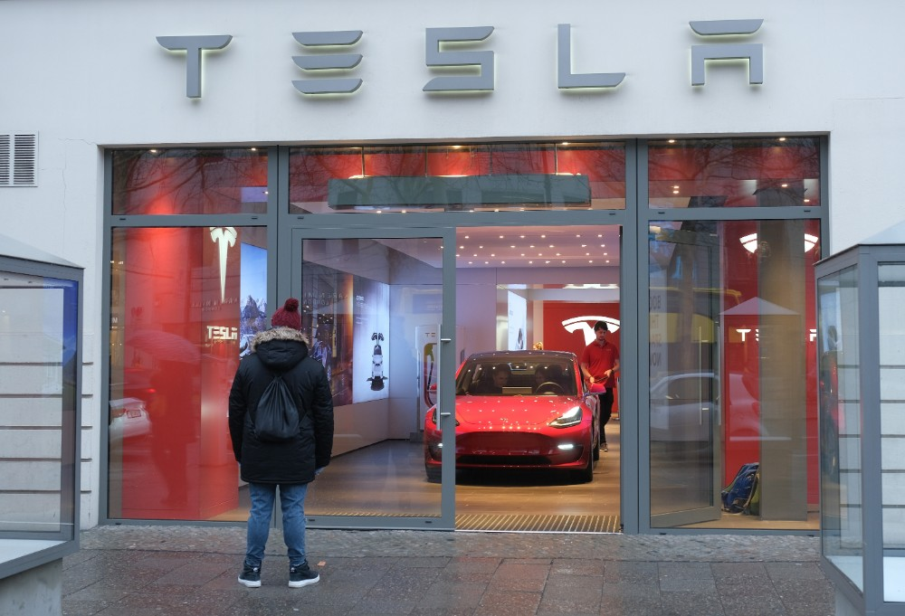 A man stands outside of a Tesla dealership in Berlin. California-based Tesla is building a new factory just outside the city and is hoping to increase its presence in the European market. Credit: Sean Gallup/Getty Images