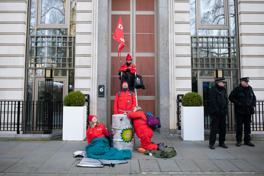 Greenpeace activists are seen chained to oil drums after the environmental group blockaded the BP headquarters with solar panels and boards, on Feb. 5, 2020 in London, England. Credit: Leon Neal/Getty Images