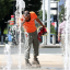 A construction worker stops to cool off in the water fountains at Canal Park, on July 19, 2019 in Washington, D.C. Credit: Mark Wilson/Getty Images