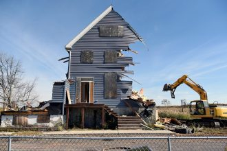 "A home demolition in Oakwood Beach, Staten Island in 2015. Image Credit: Still image from ""Managed Retreat"" by Nathan Kensinger"