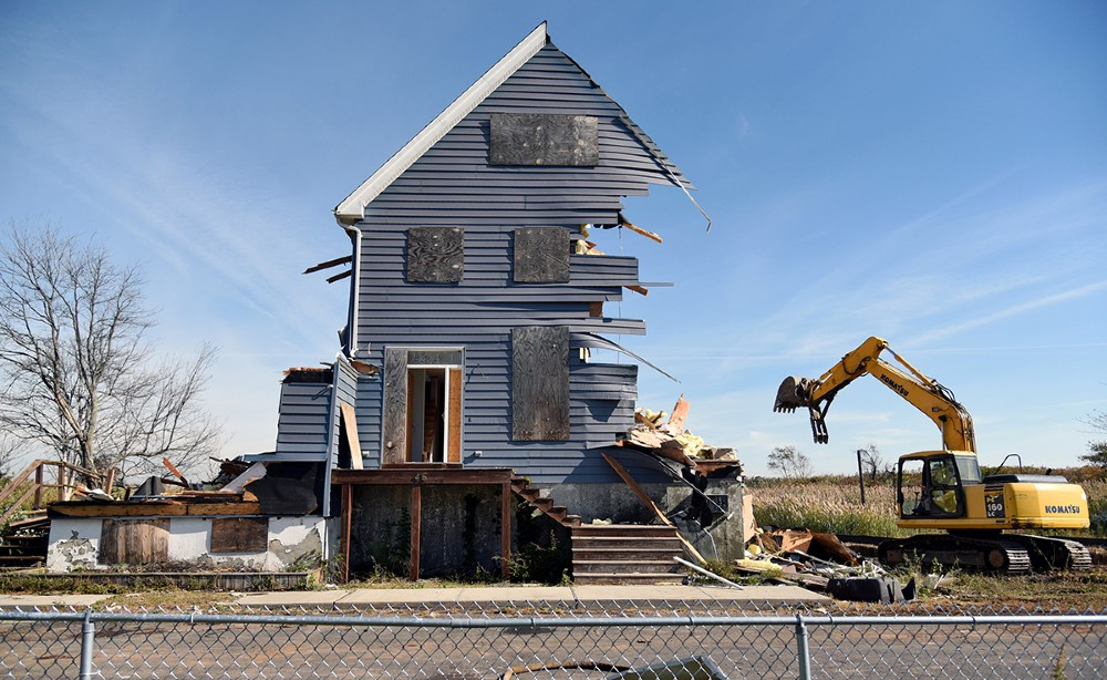 """A home demolition in Oakwood Beach, Staten Island in 2015. Image Credit: Still image from """"Managed Retreat"""" by Nathan Kensinger"""