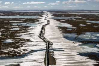 An oil pipeline stretches across the landscape outside Prudhoe Bay in North Slope Borough, Alaska on May 25, 2019. Credit: Bonnie Jo Mount/The Washington Post via Getty Images