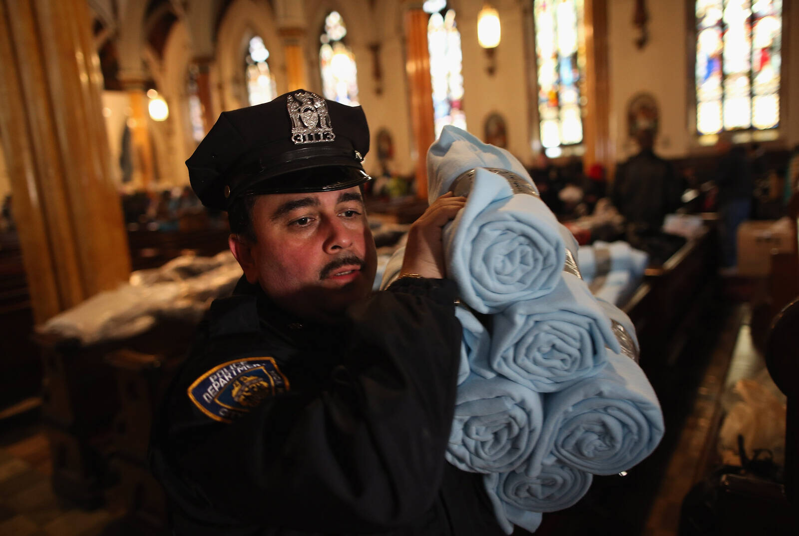 A policeman carries blankets for people affected by Superstorm Sandy on November 8, 2012 in the Brooklyn borough of New York City. Credit: John Moore/Getty Images