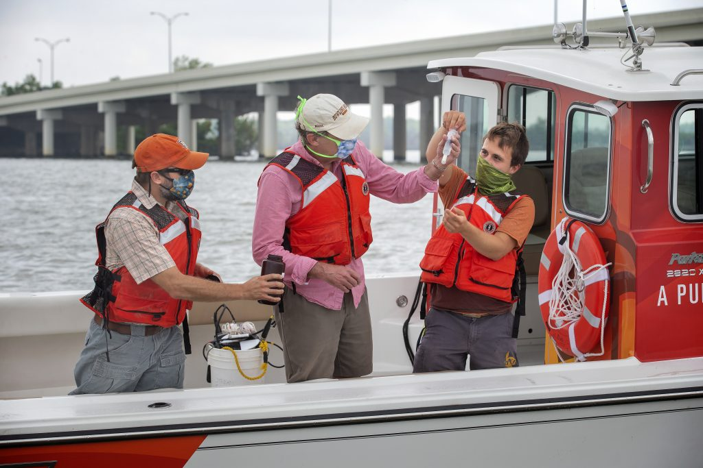 Bowling Green State University's Lake Erie Center for Fresh Waters and Human Health's research professors Tim Davis (left) and George Bullerjahn (center) along with BGSU student, Dan Peck (right) conduct water sampling on Sandusky Bay near Sandusky, Ohio,