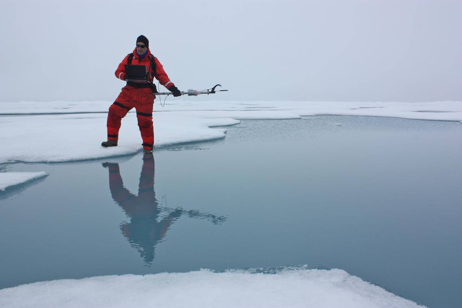 A researcher uses a spectroradiometer to measure the amount of sunlight reflected from the surface of ice and melt ponds in the Chukchi Sea. Credit: NASA/Kathryn Hansen