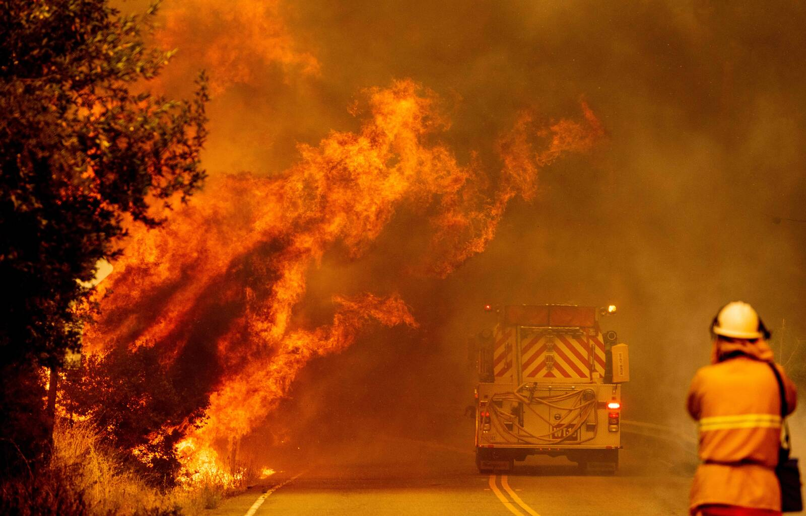 A fire truck drives through flames as the Hennessey fire continues to rage out of control near Lake Berryessa in Napa, California on August 18, 2020. Credit: JOSH EDELSON/AFP via Getty Images