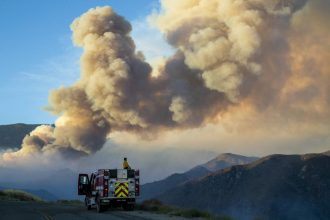 A firefighter from Carpinteria monitors the huge plume from the out-of-control Apple fire along Bluff Street, north of Banning during the coronavirus pandemic on August 1, 2020 in Cherry Valley, California. Credit: Gina Ferazzi / Los Angeles Times via Ge