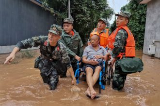 China's paramilitary police officers evacuate a resident on a flooded street following heavy rain in Meishan in China's southwestern Sichuan province. Credit: STR/AFP via Getty Images