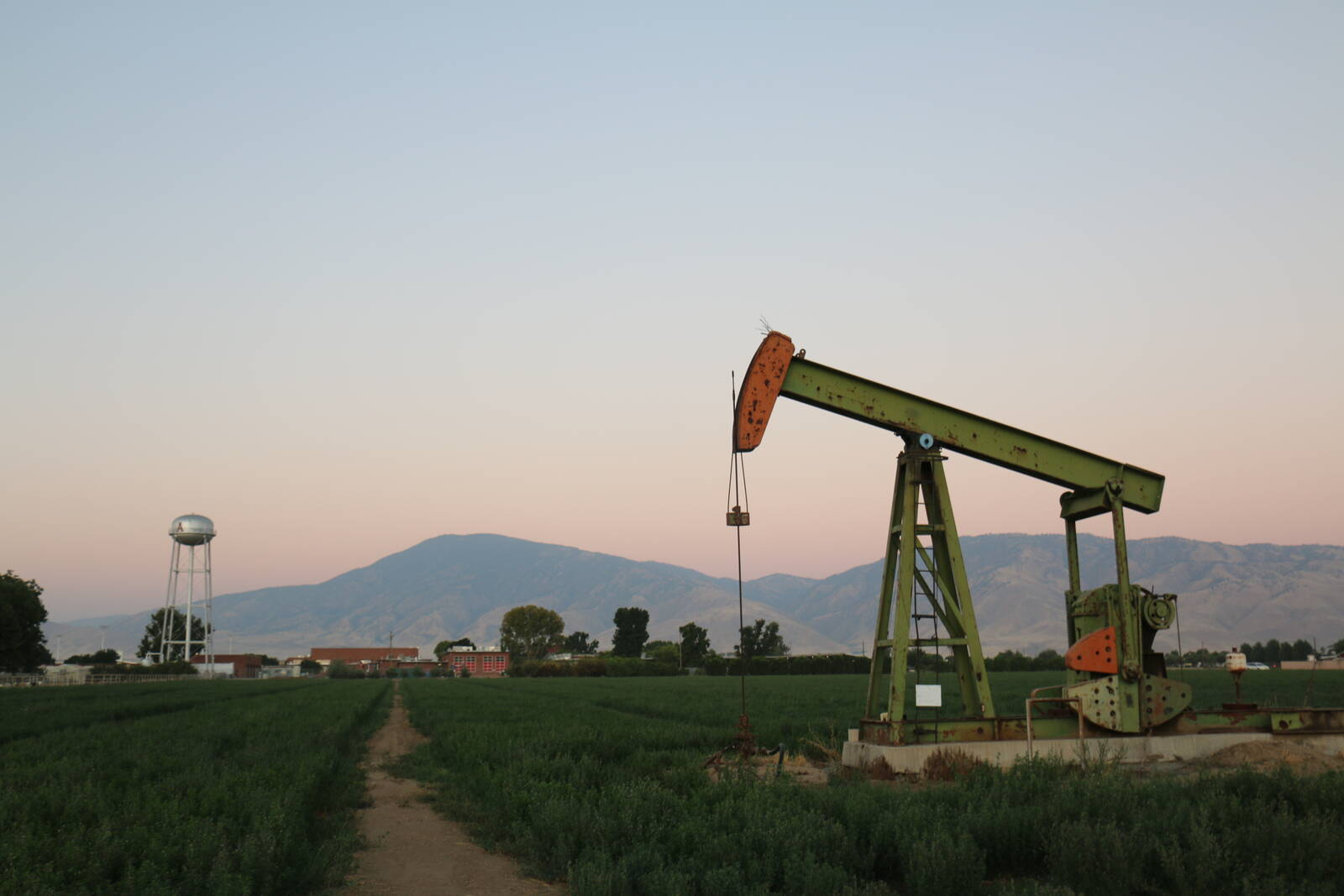 A pumpjack stands in a field next to Arvin High School with the Tehachapi Mountains in the background. Credit: Julia Kane
