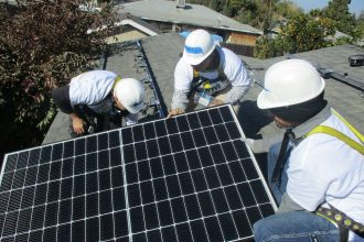 Volunteers for the nonprofit Grid Alternatives install solar panels on a house in Farmersville, California. Credit: Grid Alternatives