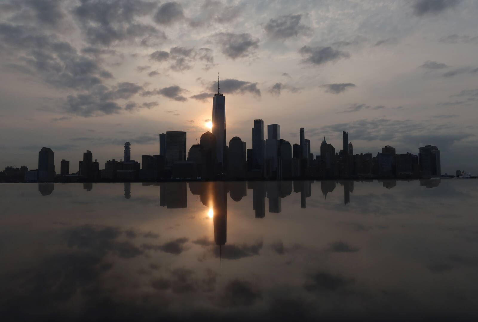 The sun rises behind the skyline of lower Manhattan and One World Trade Center in a haze created by smoke from west coast wildfires in New York City on September 17, 2020.