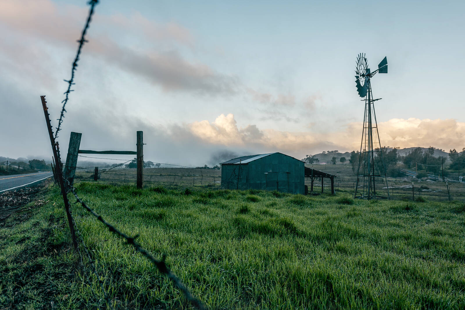 Barn and windmill of a farm seen through a fence at sunrise in Ballena in California. Credit: Mickey Strider/Loop Images/Universal Images Group via Getty Images