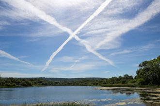 Contrails from airplanes cross in the sky on June 2, 2020 in Aylesbury, United Kingdom. Credit: Catherine Ivill/Getty Images