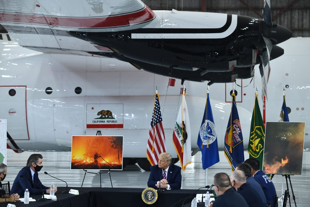 President Donald Trump listens to California Governor Gavin Newsom at Sacramento McClellan Airport in McClellan Park, California on Sept. 14, 2020 during a briefing on wildfires. Credit: Brendan Smialowski/AFP via Getty Images