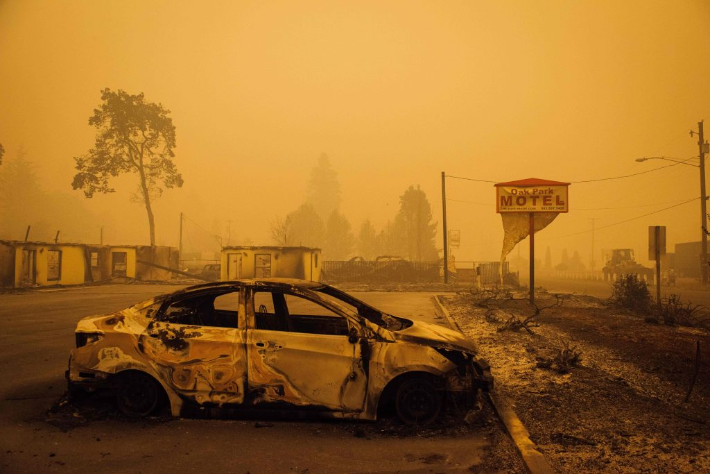 A charred vehicle is seen in the parking lot of the burned Oak Park Motel after the passage of the Santiam Fire in Gates, Oregon, on September 10, 2020. Credit: Kathryn Elsesser/AFP via Getty Images