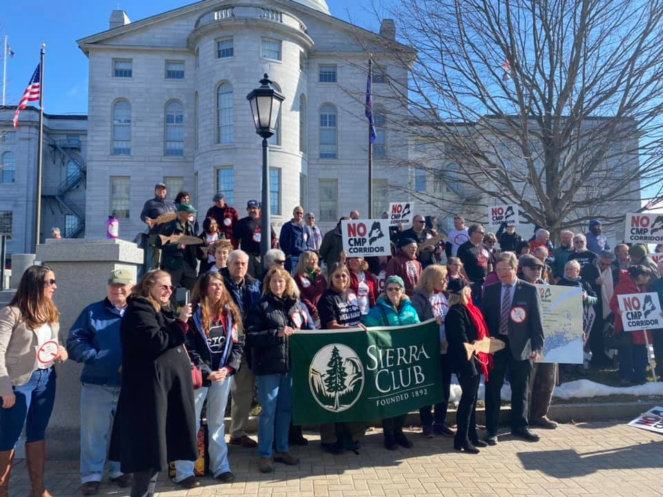 Activists who oppose New England Clean Energy Connect, a project that would bring Canadian hydropower through Maine to Massachusetts as a means of making the state's energy mix greener and more climate friendly. Some hold placards that say no CMP corridor