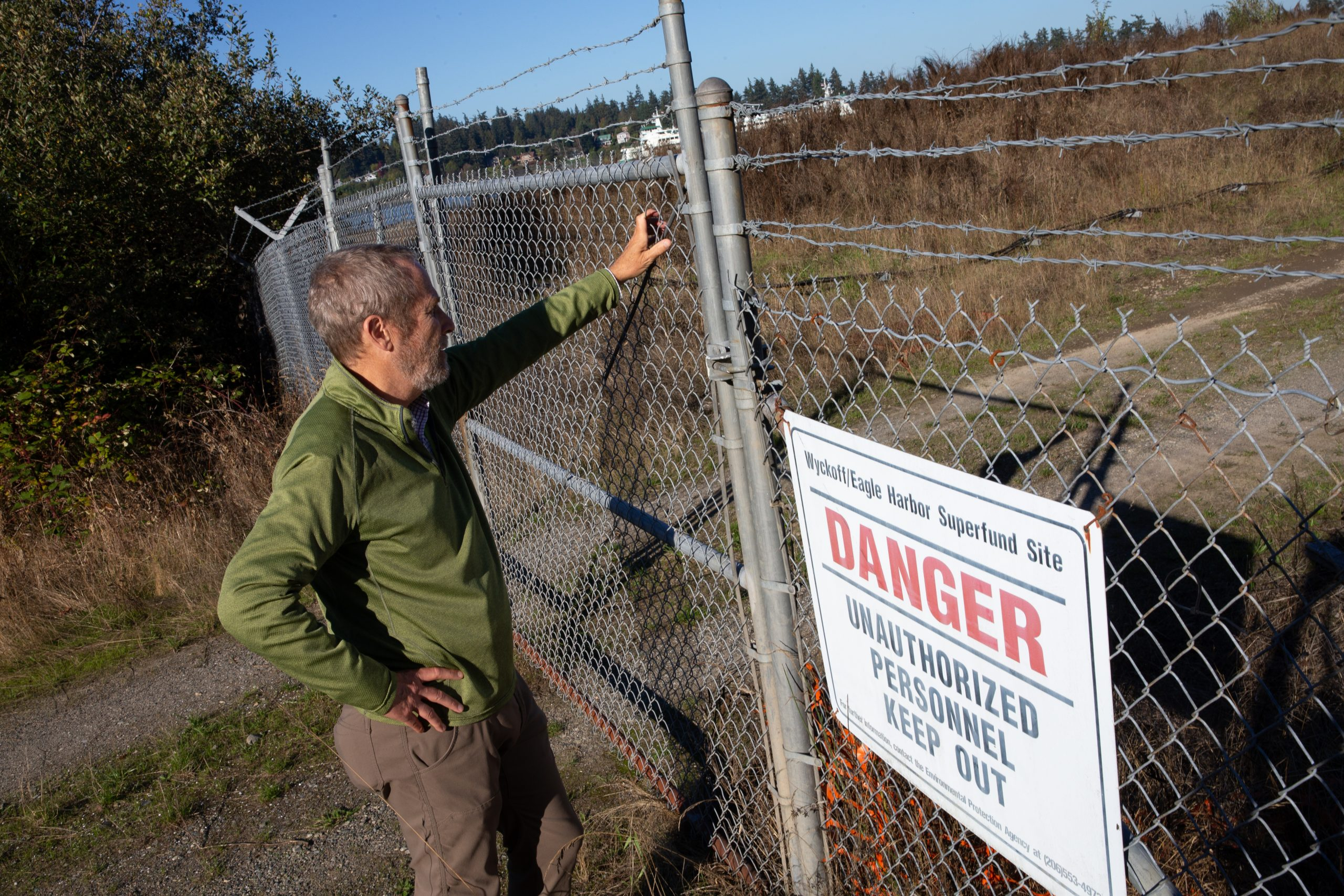 Michael Cox, a former EPA climate expert for the Pacific Northwest, looks into the Wyckoff/Eagle Harbor Superfund site on Bainbridge Island, Washington on Oct. 6, 2020. Credit: Karen Ducey