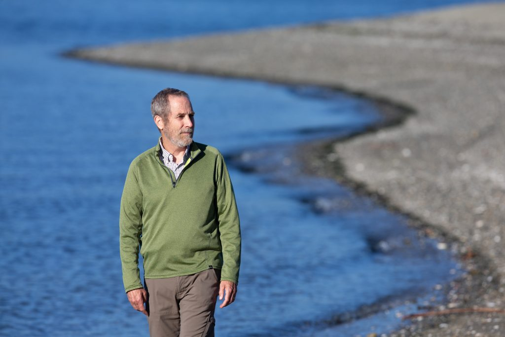 Michael Cox, a former EPA climate expert for the Pacific Northwest, walks on a beach by the Wyckoff/Eagle Harbor Superfund site on Bainbridge Island, Washington on Oct. 6, 2020. Credit: Karen Ducey