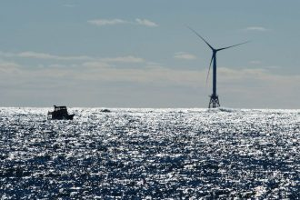 A boat passes one of the wind turbines of the Block Island Wind Farm on Oct. 14, 2016 off the shore of Rhode Island. Credit: Don Emmert/AFP via Getty Images