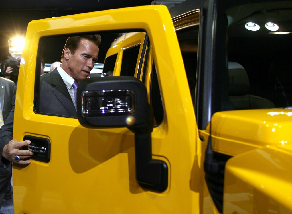 Arnold Schwarzenegger looks at a Hummer H3 in 2006. Credit: Gabriel Bouys/AFP via Getty Images
