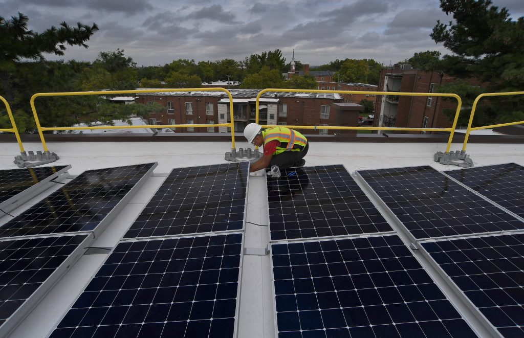 A worker installs solar panels on the roof of an apartment complex in Washington D.C. on Aug. 27, 2019. Credit: Michael S. Williamson/The Washington Post via Getty Images