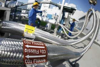 Two employees work on pipes carrying liquid CO2 on Sept 8, 2008 at a power station near Berlin, Germany. Credit: Michael Urban/DDP/AFP via Getty Images