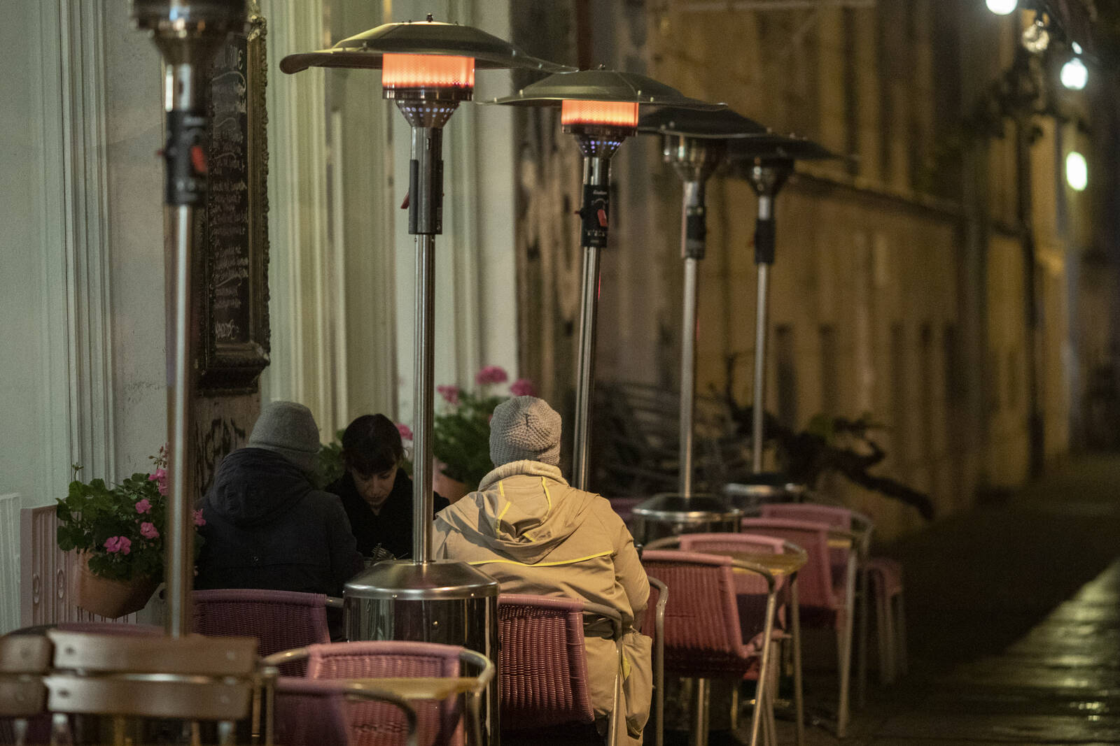 People sit outside a restaurant that uses umbrella heaters on October 15, 2020 in Berlin, Germany. Credit: Maja Hitij/Getty Images