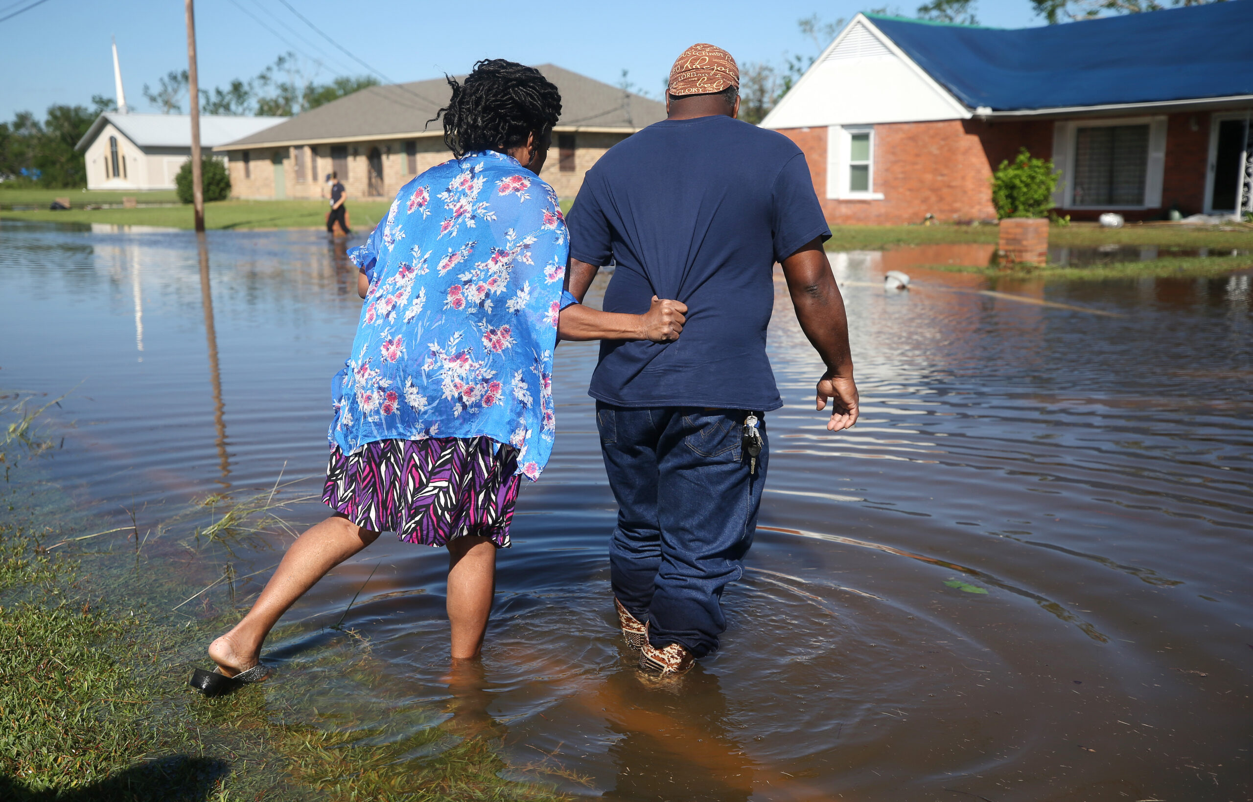 Patrick King and Soncia King walk through flood waters from Hurricane Delta toward their home (R) which they were still repairing from damage from Hurricane Laura on October 10, 2020 in Lake Charles, Louisiana. C