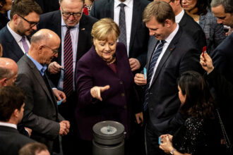 German Chancellor Angela Merkel throws her voting card into the ballot box during passage of sweeping climate legislation in December 2019.