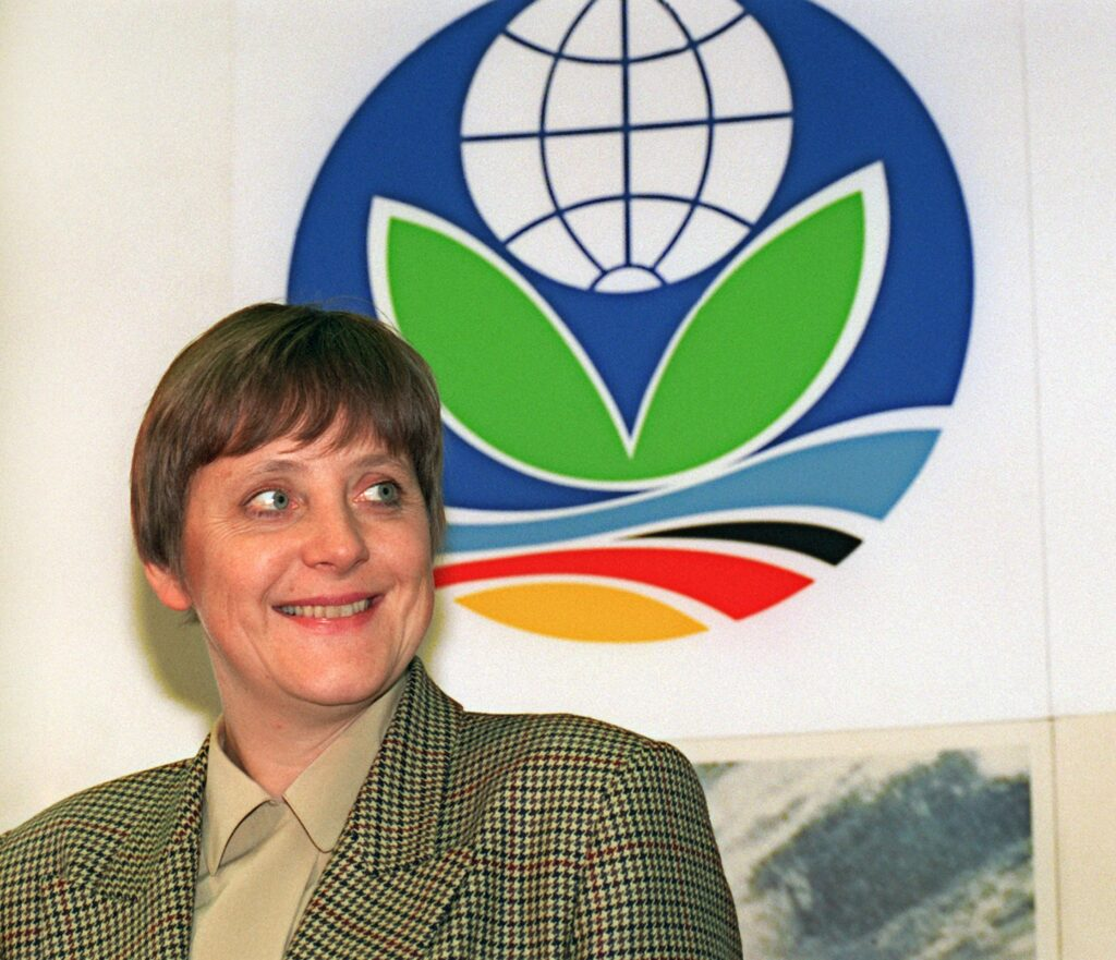 Then-German Environment Minister Angela Merkel stands next to the logo of the UN climate conference, in Berlin, Germany, on March 8, 1995. Credit: Martin Gerten/picture alliance via Getty Images