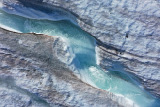 In this aerial view from a drone water carves a winding channel down the surface of the melting Longyearbreen glacier during a summer heat wave on Svalbard archipelago on July 31, 2020 near Longyearbyen, Norway. Credit: Sean Gallup/Getty Images