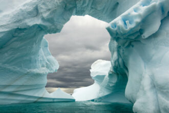 An arched iceberg floating off the Western Antarctic peninsula, Antarctica, Southern Ocean. Credit: Steven Kazlowski/Barcroft Media/Getty Images