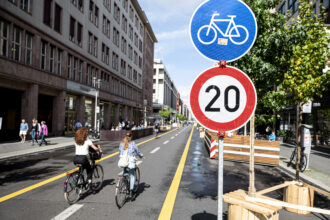 Two cyclists ride on the car-free section of Friedrichstraße in Berlin, where a speed limit of 20 kilometers per hour (12 mph) applies. Credit: Fabian Sommer/picture alliance via Getty Images