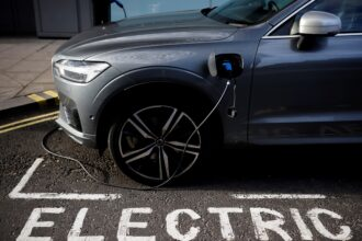 A charging cable is plugged into a Volvo electric vehicle in London on Nov. 18, 2020. Credit: Tolga Akmen/AFP via Getty Images