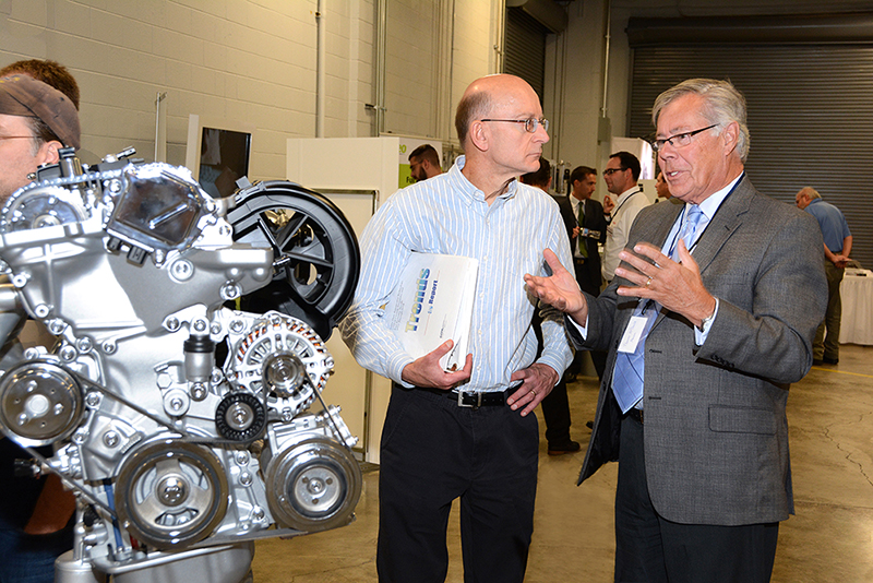Jeff Alson discusses energy efficiency advances with an auto industry representative at a 2014 technology showcase at EPA's National Vehicle Fuel Economy Laboratory in Ann Arbor, Michigan. Credit: EPA