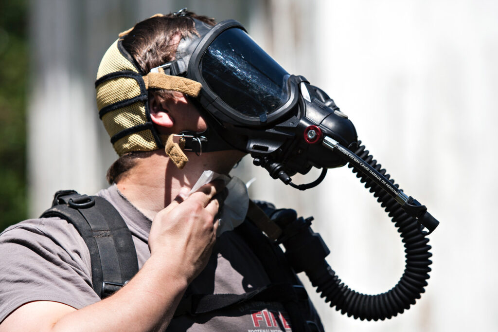 A wildland firefighting crew member from the Libby Ranger District on the Kootenai National Forest trains with the respirator he must use when deployed to fight fires in the forests of Operable Unit 3 of the Libby Asbestos Superfund site on June 1, 2015. Credit: Greg Lindstrom/Flathead Beacon
