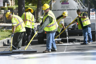 Jordan Avenue, north of Hart Street is getting a new surface coating similar to slurry seal on May 20, 2017 in Canoga Park, California. Instead of traditional black asphalt, this coat is a concrete color designed to reflect heat. Credit: John McCoy/MediaNews Group/Los Angeles Daily News via Getty Images