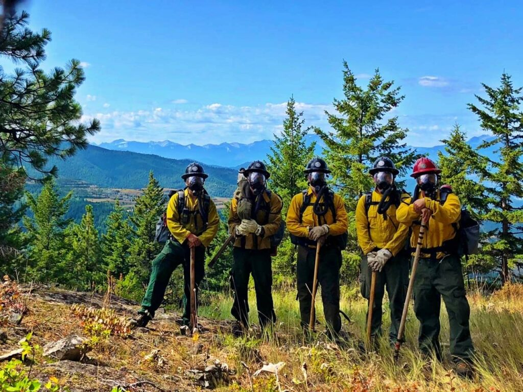 Nolan Buckingham, right, led a crew of firefighters in Operable Unit 3 of the Libby Asbestos Superfund site, which required them to wear respirators to protect them from the asbestos contaminating the tree bark, soils and duff of the forest. The mine behind them in the background produced vermiculite that was contaminated with asbestos. More than 400 people in the area have died of asbestos-related diseases. Photo Courtesy of Nolan Buckingham