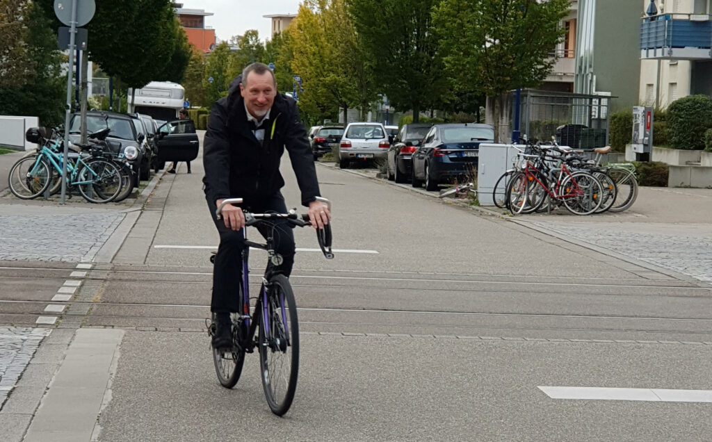 Wolfgang Teubner, a regional director for the sustainability nonprofit ICLEI, rides his bike in the Rieselfeld neighborhood of Freiburg where he lives. Rieselfeld and Vauban are two neighborhoods in the city that were designed to accommodate biking, walking and public transport, and de-emphasize cars. Courtesy of Wolfgang Teubner