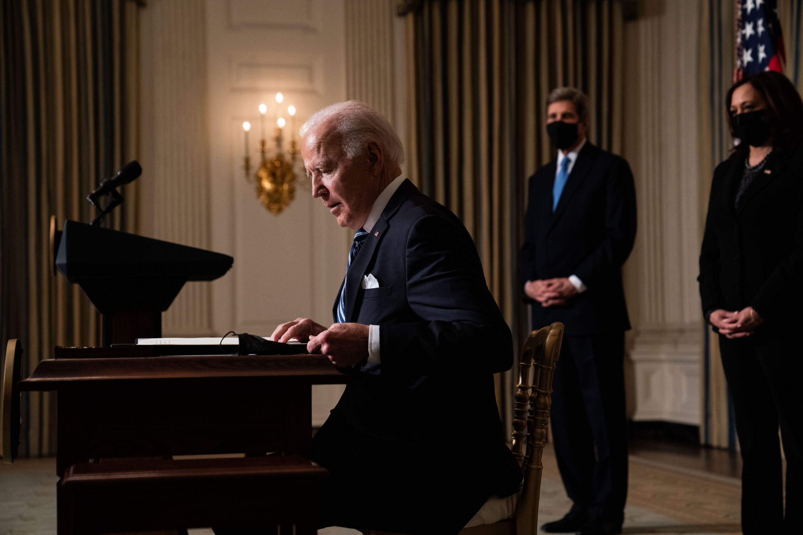 U.S. President Joe Biden prepares to sign executive orders after speaking about climate change issues in the State Dining Room of the White House on January 27, 2021 in Washington, DC. President Biden signed several executive orders related to the climate change crisis on Wednesday, including one directing a pause on new oil and natural gas leases on public lands. Also pictured, left to right, Special Presidential Envoy for Climate John Kerry and Vice President Kamala Harris. Credit: Anna Moneymaker-Pool/Getty Images