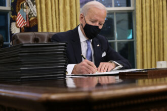 U.S. President Joe Biden prepares to sign a series of executive orders, including rejoining the Paris Climate Agreement, at the Resolute Desk in the Oval Office just hours after his inauguration on January 20, 2021 in Washington, DC. Biden became the 46th president of the United States earlier today during the ceremony at the U.S. Capitol. Credit: Chip Somodevilla/Getty Images