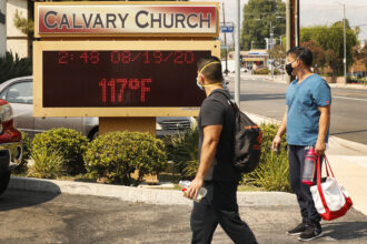 Anthony Aco and Troy Sacaguin, left to right, check out the thermometer at Calvary Church in Woodland Hills as it registers 117 degrees Fahrenheit on Wednesday, Aug. 19, 2020 in Woodland Hills, California. Credit: Al Seib/Los Angeles Times