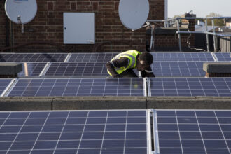 Re-Powering intern and an estate resident with the solar photo voltaic panels on the roof of Hackney council estate Bannister House, the first community solar installation on an estate in Hackney, London, United Kingdom. Credit: Andrew Aitchison/In pictures via Getty Images