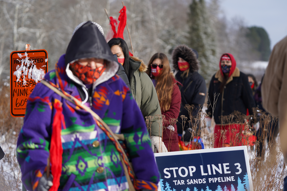 Protesters of Enbridge Energy's Line 3 replacement project walk through the project's construction zone near Palisade, Minnesota. The oil pipeline will stretch through 337 miles in northern Minnesota. Credit: Nedahness Greene